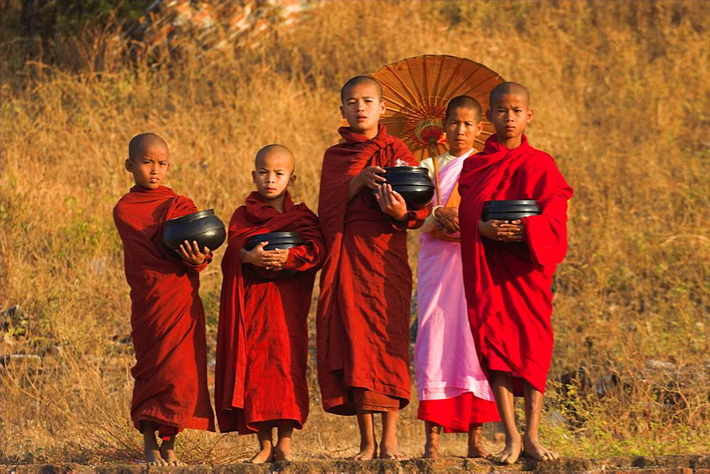 Nun with novice monks holding alms bowls at Mingun Paya, Mingun, Mandalay, Myanmar (Burma), Asia