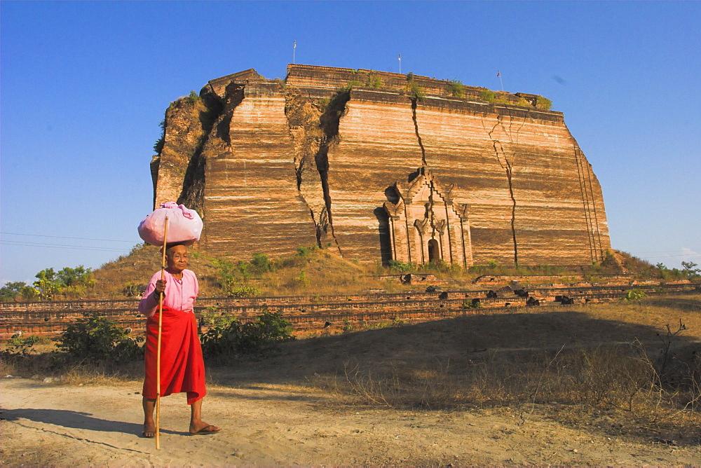 Elderly nun walks past paya with aid of walking stick, Mingun Paya, Mingun, Mandalay, Myanmar (Burma), Asia