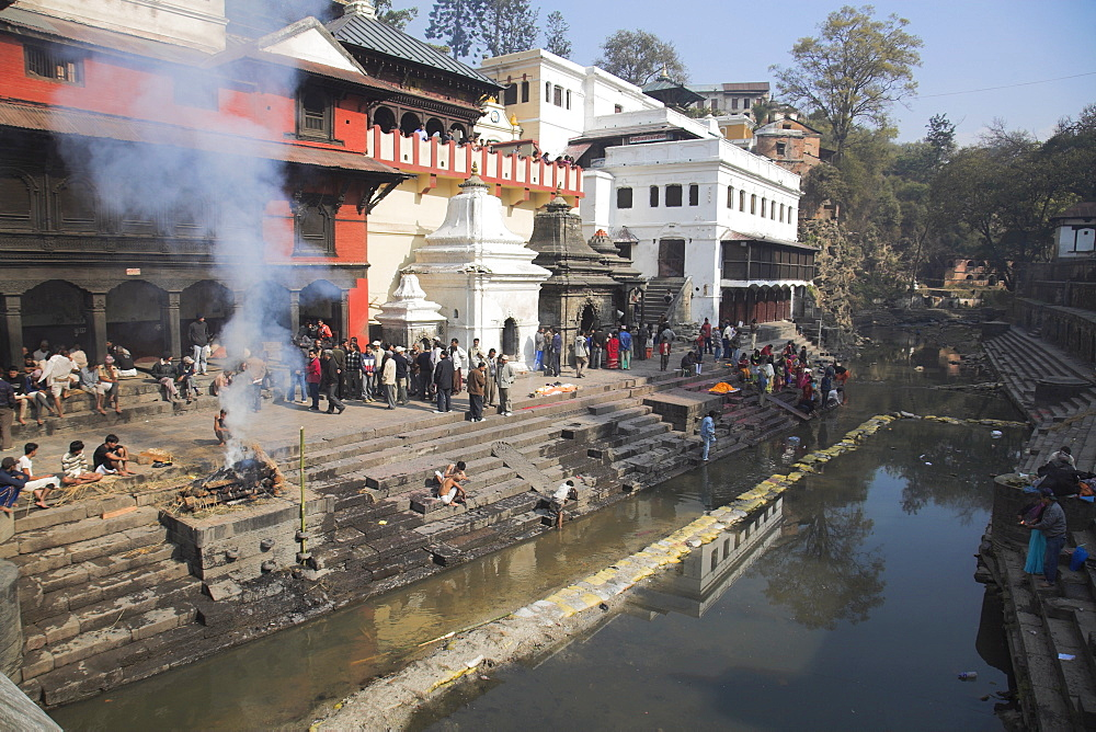 Smoke rising from cremation ceremony on banks of Bagmati River during Shivaratri festival, Pashupatinath Temple, Kathmandu, Nepal, Asia