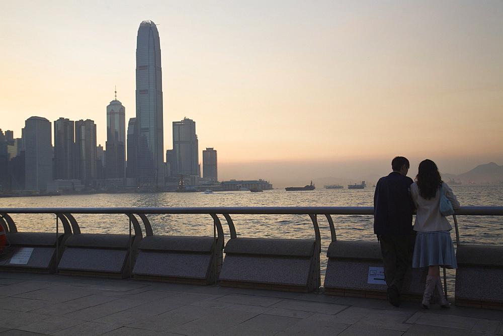 Couple looking at Victoria Bay and city skyline at sunset, Hong Kong, China, Asia