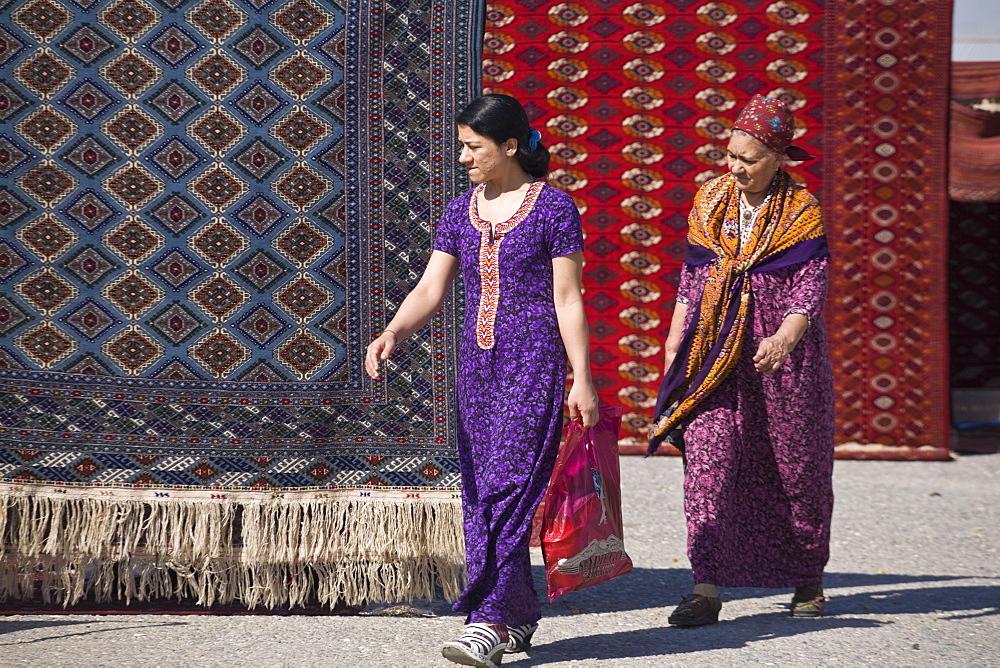 Women walking past carpets, Tolkuchka Bazaar, Turkmenistan, Central Asia, Asia