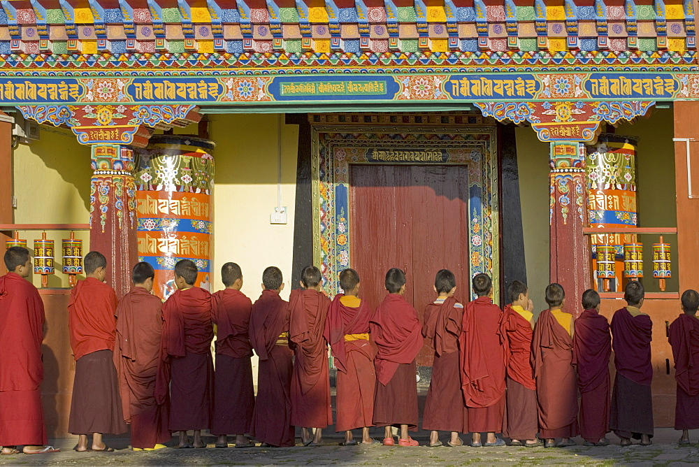 Novice monks line up in front of monastic building at the new Karma Theckhling Monastery, built in traditional Sikkim style, Ravangla (Rabongla), Sikkim, India, Asia
