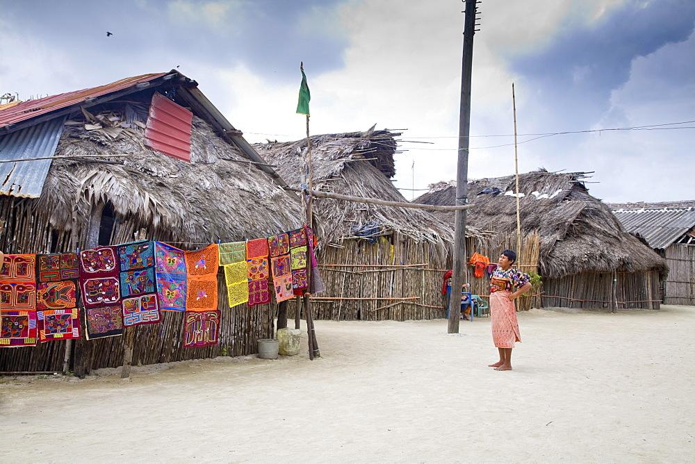 Molas hanging up for sale outside thatched houses, Isla Tigre, San Blas Islands, Comarca de Kuna Yala, Panama, Central America