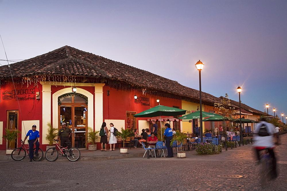 Man rideing bike past restaurant on Calle La Calzada, Granada, Nicaragua, Central America