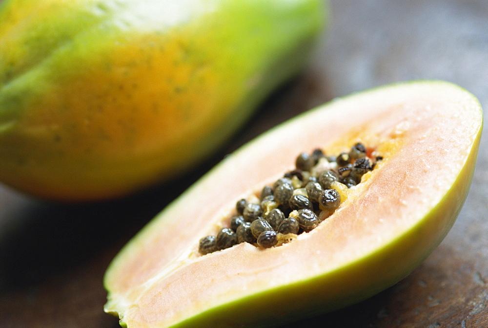 Close-up of a papaya sliced in half showing black seeds inside