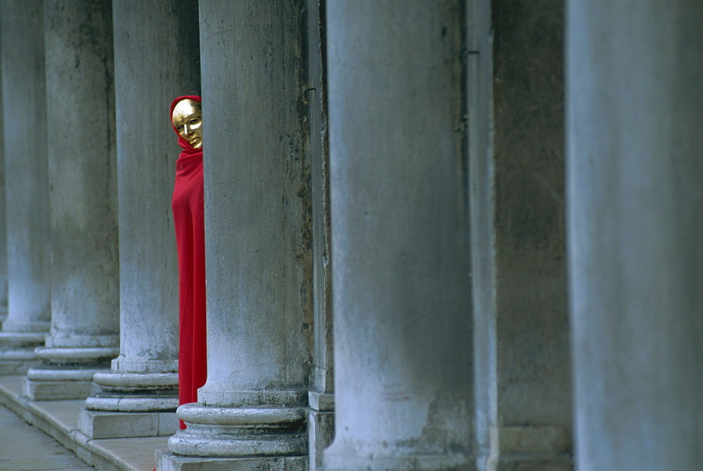Carnival model in red cape and gold mask peering from columns in St. Mark's Square, Venice, UNESCO World Heritage Site, Veneto, Italy, Europe - 321-2958