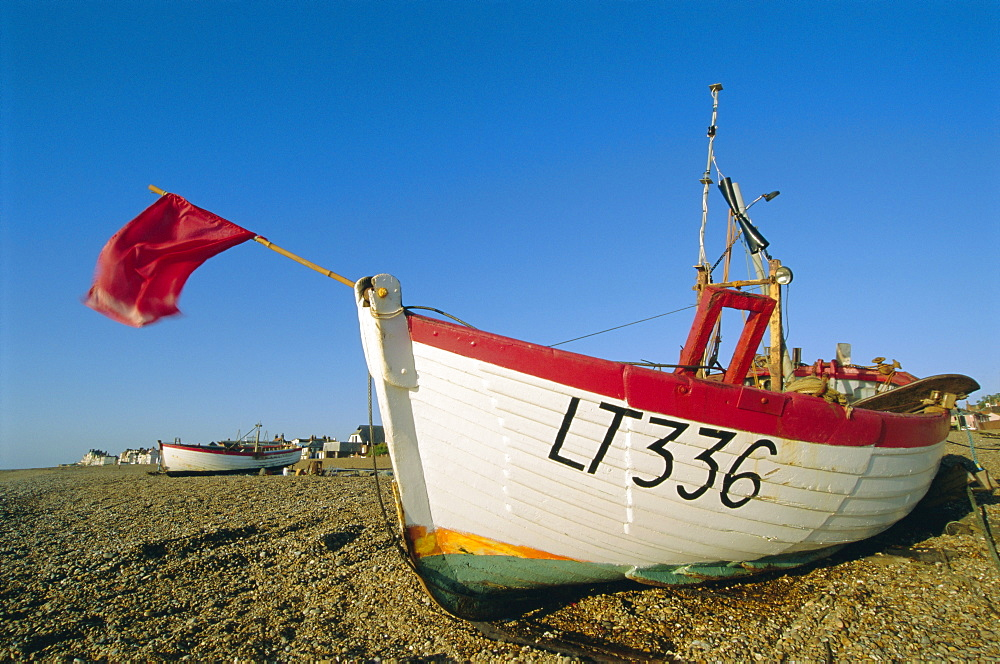 Fishing boat with red flag on the beach, Aldeburgh, Suffolk, England, UK, Europe