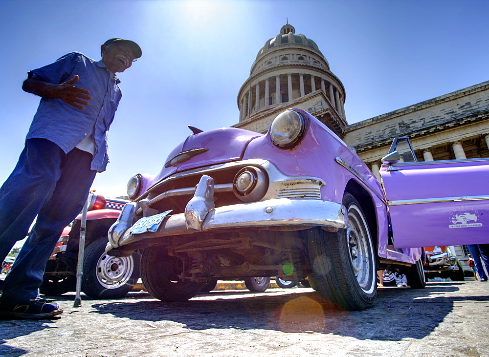 Low angle shot of The Capitolio with classic American car and old man in foreground, Havana, Cuba, West Indies, Caribbean, Central America - 321-4623