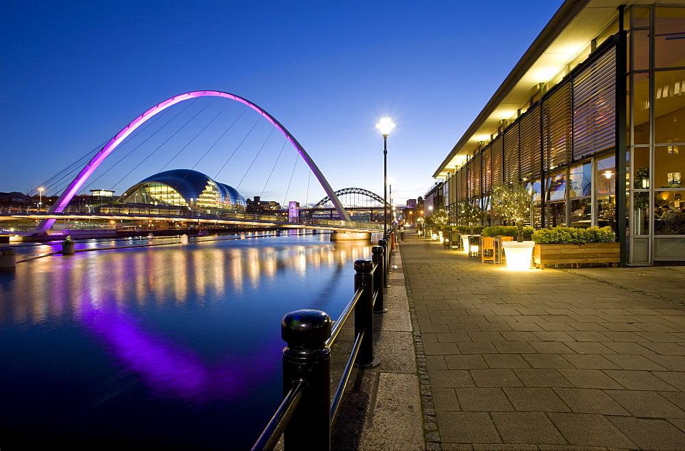 View along Newcastle Quayside at night showing the River Tyne, the floodlit Gateshead Millennium Bridge, the Arched Bridge and the Sage Gateshead, Newcastle-upon-Tyne, Tyne and Wear, England, United Kingdom, Europe