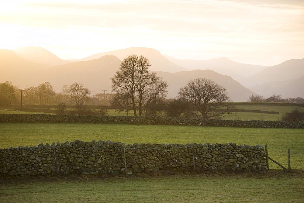 Sunset over Lakeland Fells with fields and stone walls, near Keswick, Lake District National Park, Cumbria, England, United Kingdom, Europe