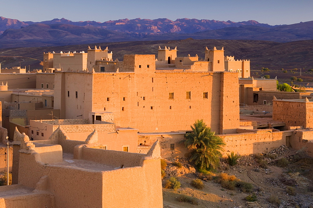 Kasbah bathed in evening light with the Jbel Sarhro Mountains in the distance, Nkob, southern Morocco, Morocco, North Africa, Africa