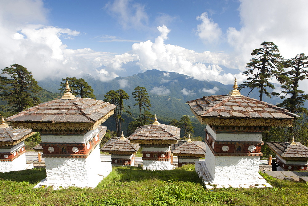 Some of the 108 Chortens located at the summit of the Dochu La Pass with views towards distant forested mountains between Thimpu and Punakha, Bhutan, Himalayas, Asia