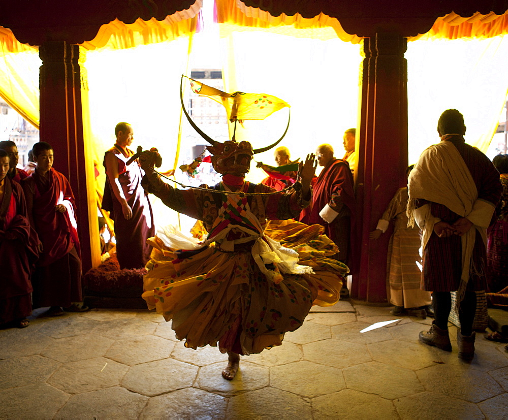 Buddhist monk in costume and mask practising his dance before taking part in a performance at the Gangtey Tsechu at Gangte Goemba, Gangte, Phobjikha Valley, Bhutan, Asia