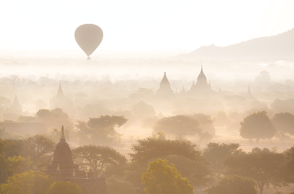 View over the temples of Bagan swathed in early morning mist, with hot air balloon drifting across the scene, from Shwesandaw Paya, Bagan, Myanmar (Burma), Southeast Asia - 321-5069