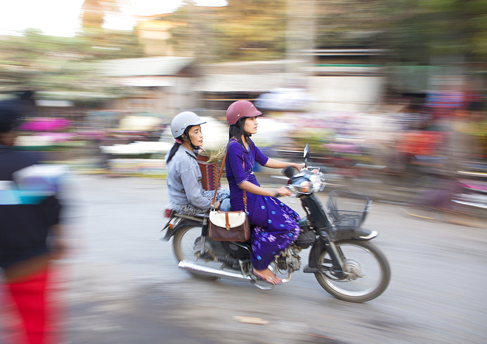 Panned and blurred shot, creating a sense of movement, of two women riding moped through a market, Mandalay, Myanmar (Burma), Asia