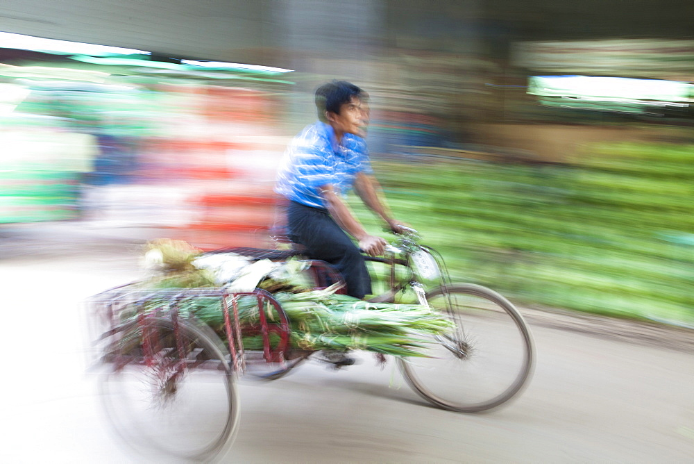 Panned and blurred image to add a sense of movement of a man cycling through Thiri Mingalar market, Yangon (Rangoon), Myanmar (Burma), Asia