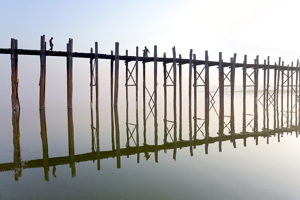 Dawn view of the famous U Bein teak bridge crossing Taungthaman Lake, the bridge reflecting in the calm water, near Mandalay, Myanmar (Burma), Asia