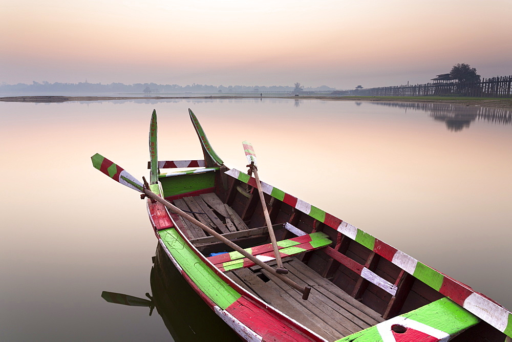 Traditional rowing boat moored on the edge of flat calm Taungthaman Lake at dawn with the colours of the sky reflecting in the calm water, close to the famous U Bein teak bridge, near Mandalay, Myanmar (Burma), Asia - 321-5102