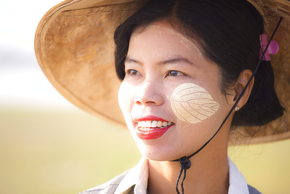 Backlit portrait of local woman wearing traditional bamboo hat and Thanaka face painting in the shape of leaves on her cheeks, near Mandalay, Myanmar (Burnma), Asia