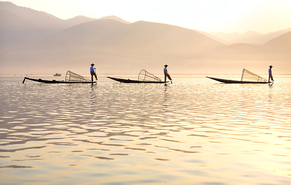 Intha 'leg rowing' fishermen at sunset on Inle Lake who row traditional wooden boats using their leg and fish using nets stretched over conical bamboo frames, Inle Lake, Myanmar (Burma), Southeast Asia - 321-5139
