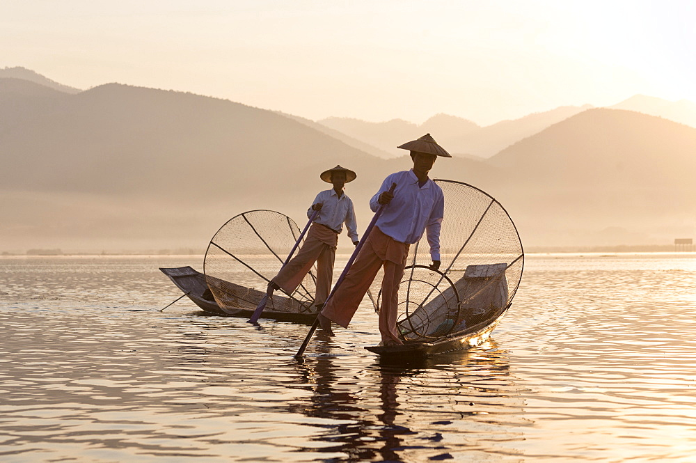 Intha 'leg rowing' fishermen at sunset on Inle Lake who row traditional wooden boats using their leg and fish using nets stretched over conical bamboo frames, Inle Lake, Myanmar (Burma), Southeast Asia - 321-5141