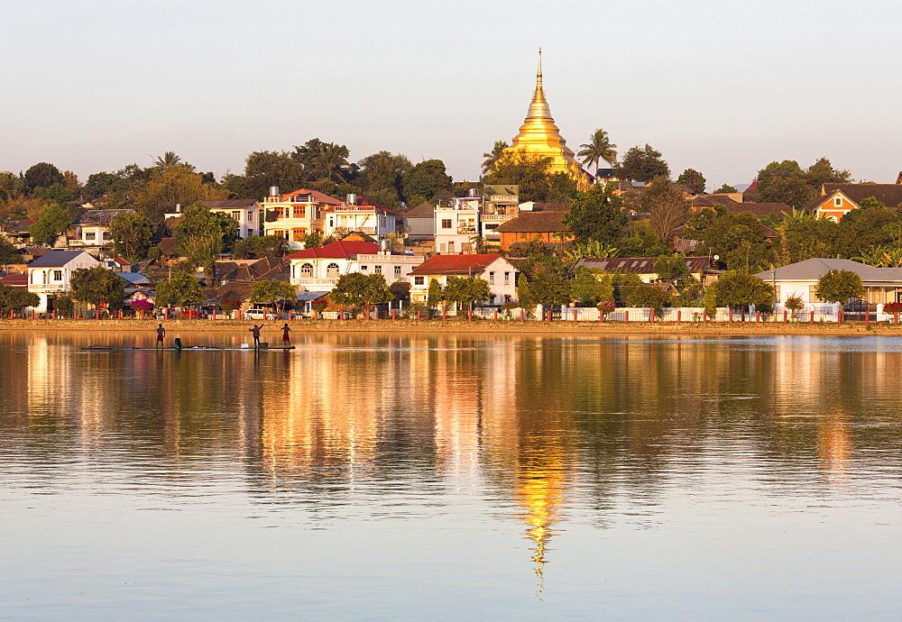 View of Kengtung (Kyaingtong) looking across Naung Tung Lake towards the town and gilded stupa of Wat Jong Kham bathed in evening light, Kengtung, Shan State, Myanmar (Burma), Asia