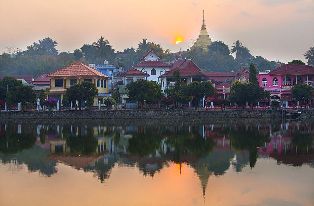 View of Kengtung (Kyaingtong) looking across Naung Tung Lake at sunrise towards the town and gilded stupa of Wat Jong Kham, Kengtung, Shan State, Myanmar (Burma), Asia