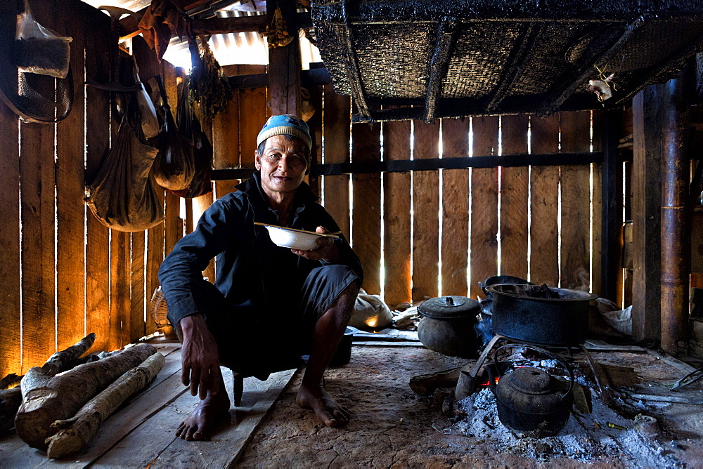 Animist man of the Ann tribe eating in his home by open fire, Panlor village, near Kengtung (Kyaingtong), Shan State, Myanmar (Burma), Asia