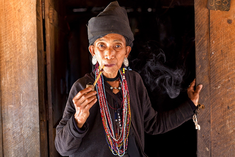 Woman of the Ann tribe in traditional black dress and colourful beads smoking a pipe in the doorway of her home in a hill village near Kengtung (Kyaingtong), Shan State, Myanmar (Burma), Asia