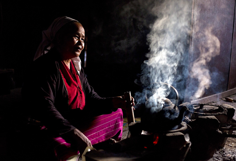 Woman of the Palaung tribe cooking on open fire in her home in village near Kengtung (Kyaingtong), Shan State, Myanmar (Burma), Asia
