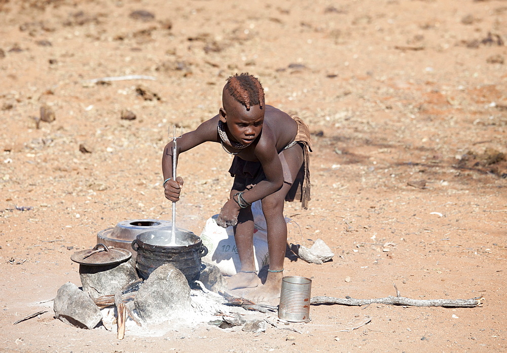 Young Himba boy cooking food on open fire in his village, Kunene Region (formerly Kaokoland) in the far north of Namibia, Africa