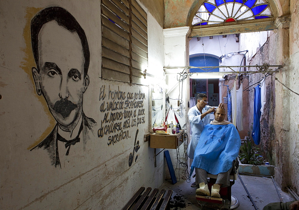 Man having haircut in backstreet barber shop, Havana Viejo, Havana, Cuba, West Indies, Central America