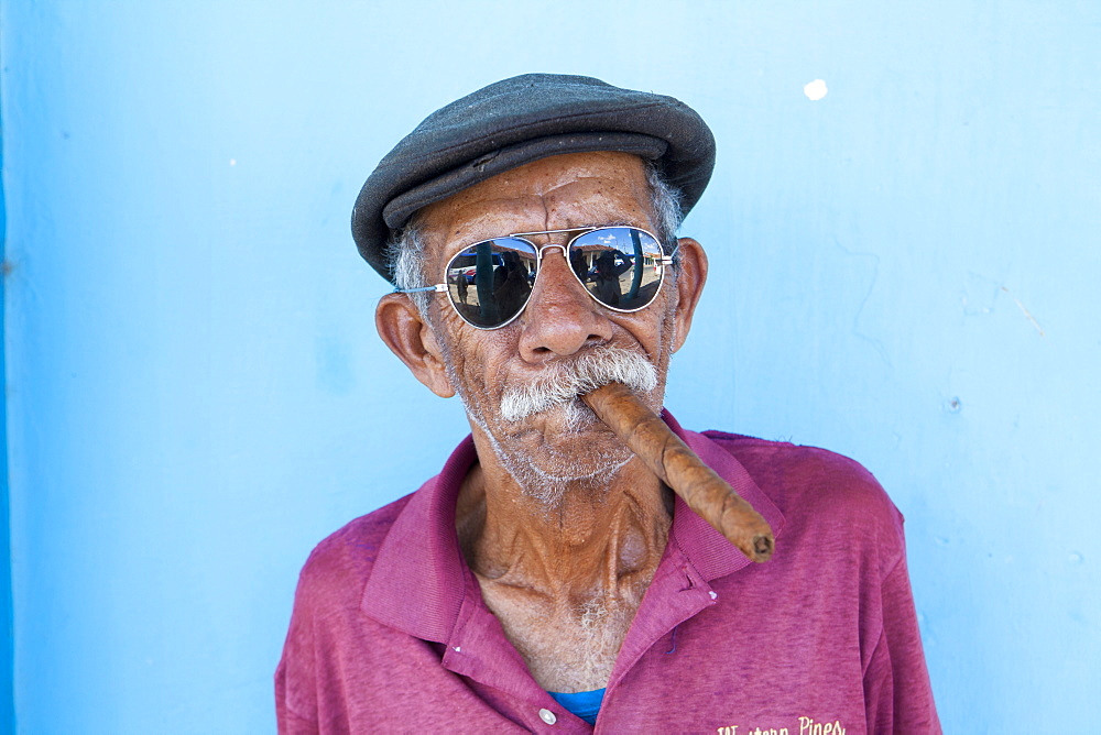 Old man wearing sunglasses and flat cap, smoking big Cuban cigar, Vinales, Pinar Del Rio Province, Cuba, West Indies, Central America