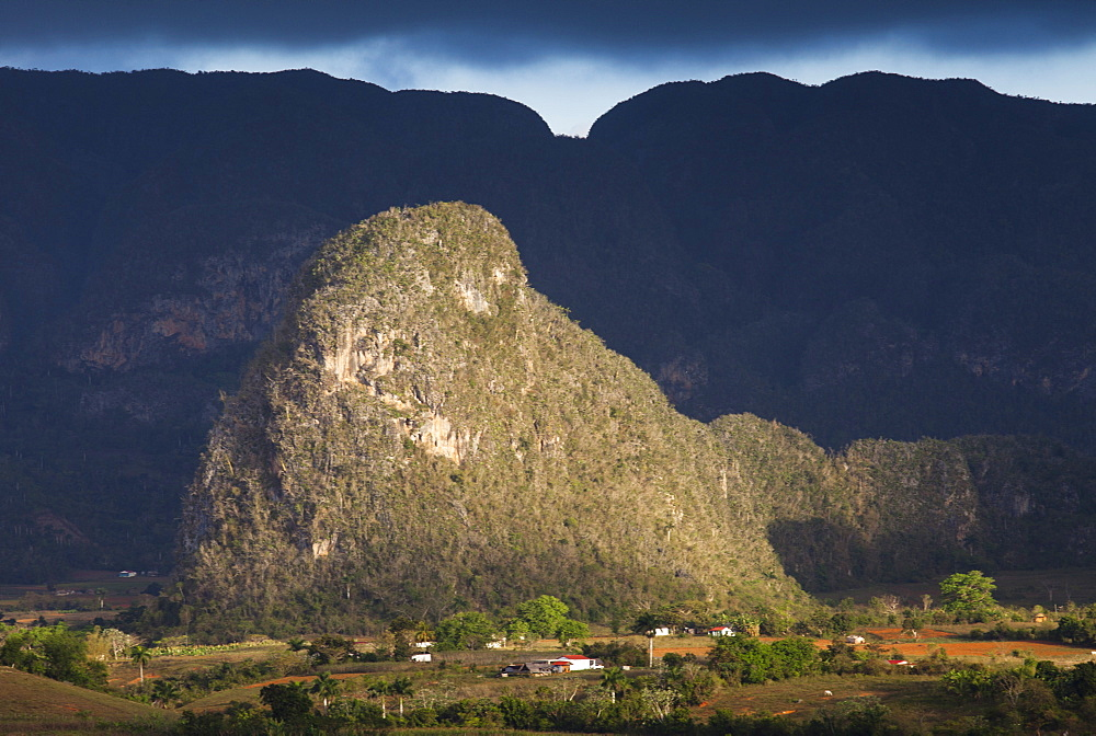 View across Vinales Valley, UNESCO World Heritage Site, from Hotel Los Jasmines in stormy weather showing one of the limestone Magotes lit by the sun against mountains in shade, Vinales, Pinar Del Rio Province, Cuba, West Indies, Central America