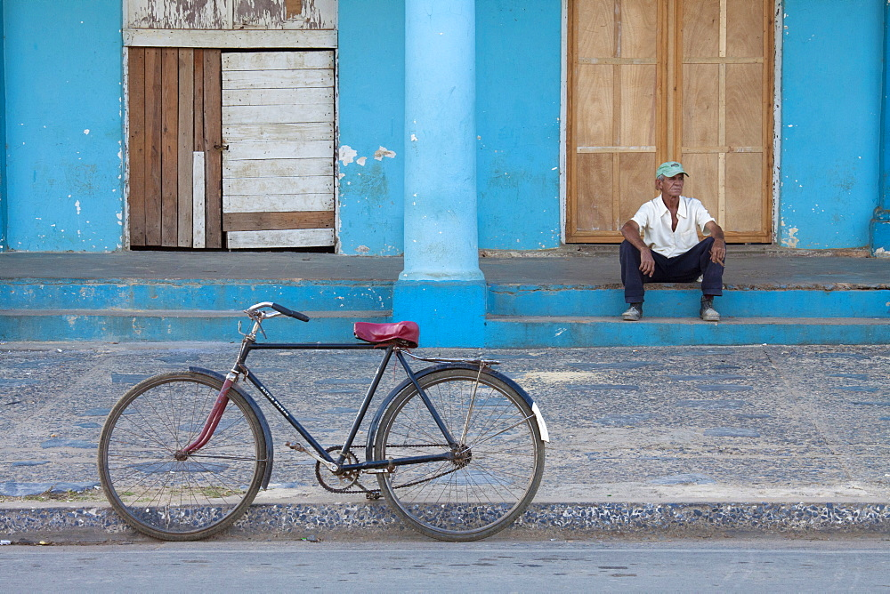 Old bicycle propped up outside old building with local man on steps, Vinales, Pinar Del Rio Province, Cuba, West Indies, Central America