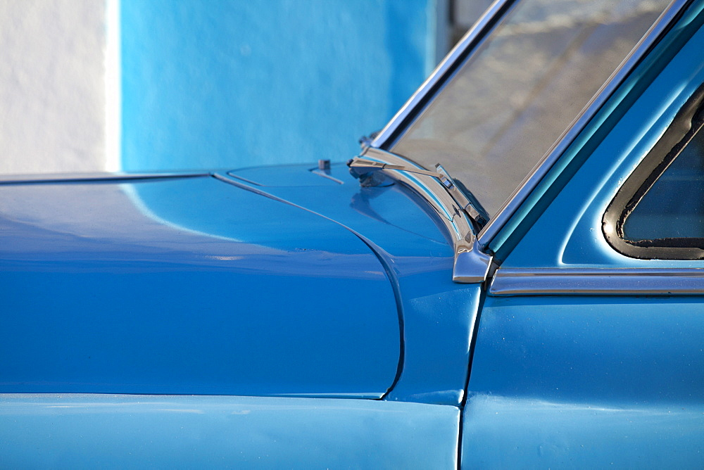 Detail of vintage blue American car against painted blue wall, Cienfuegos, Cuba, West Indies, Central America