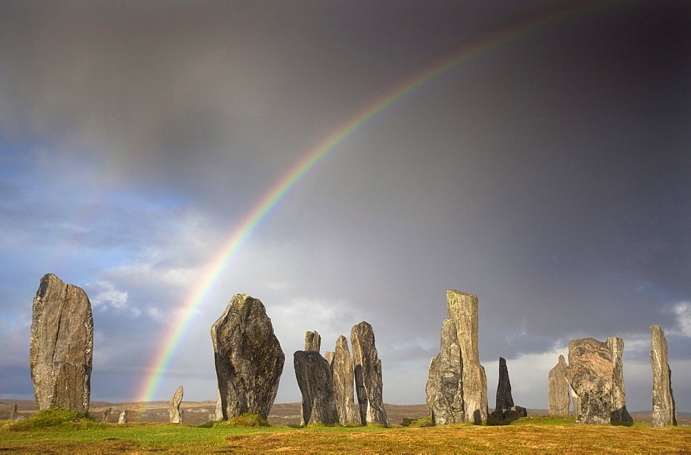 Standing Stones of Callanish bathed in sunlight with a rainbow arching across the sky in the background, near Carloway, Isle of Lewis, Outer Hebrides, Scotland, United Kingdom, Europe