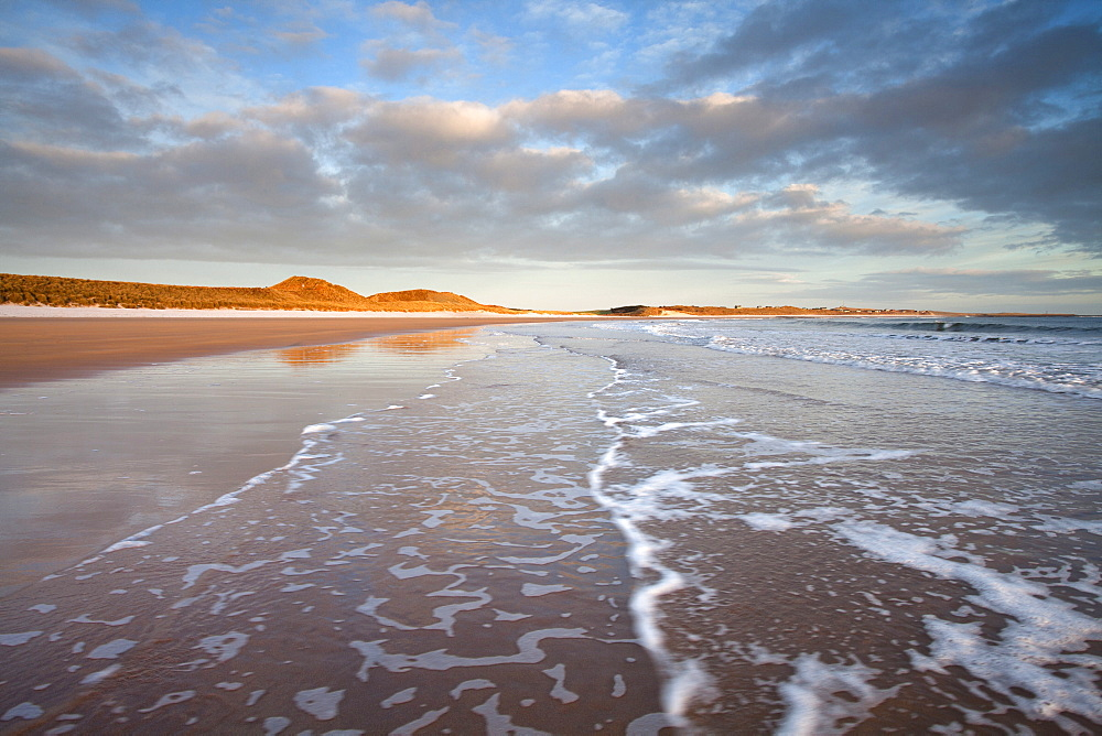 Looking across Embleton Bay just after sunrise towards the sunlit sand dunes at Embleton and Low Newton, with gentle waves washing up the beach in the foreground, Embleton, near Alnwick, Northumberland, England, United Kingdom, Europe