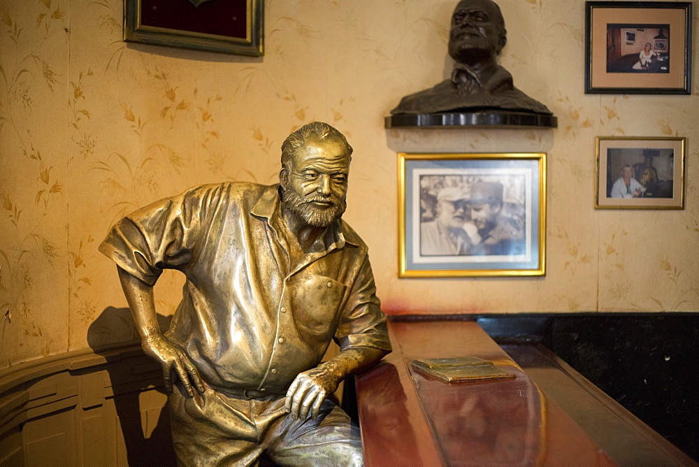 Lifesize bronze of the late author Ernest Hemingway at the bar of El Floridita, one of his favourite haunts, Havana, Cuba, West Indies, Central America