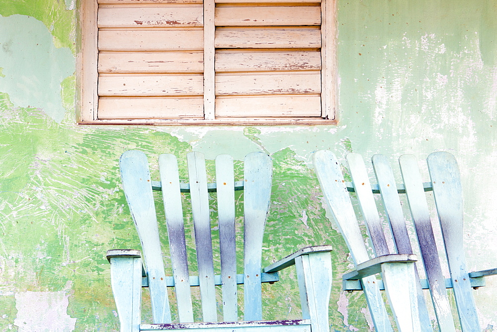 Detail of wall and rocking chair with faded paintwork in green and blue, a common sight in the small town of Vinales, Pinar Del Rio Province, Cuba, West Indies, Central America
