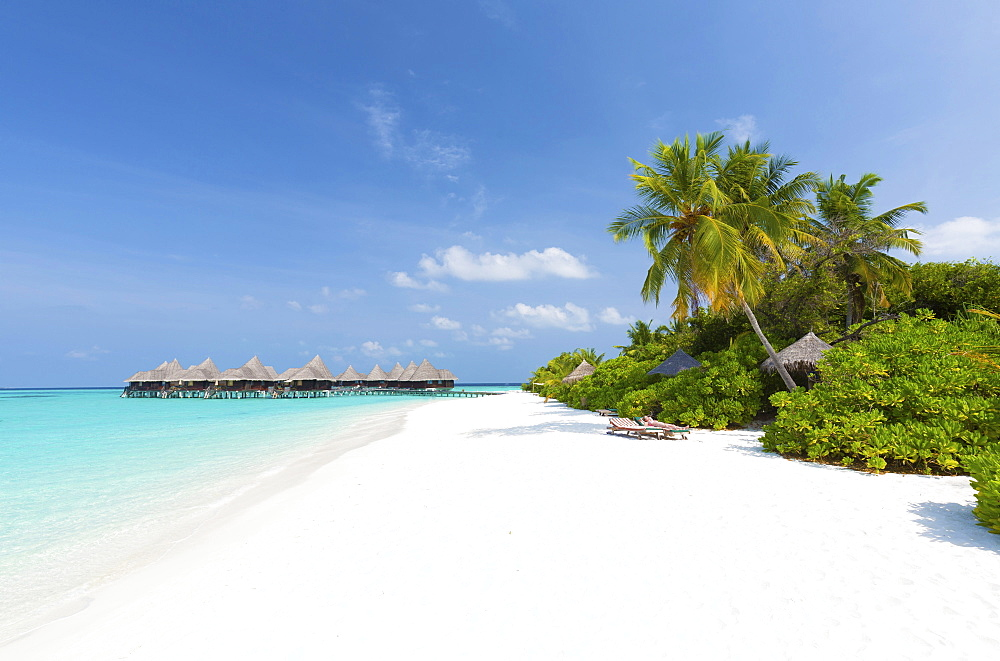View along tropical beach towards over-water villas, Coco Palm Resort, Dhuni Kolhu, Baa Atoll, Republic of Maldives, Indian Ocean, Asia
