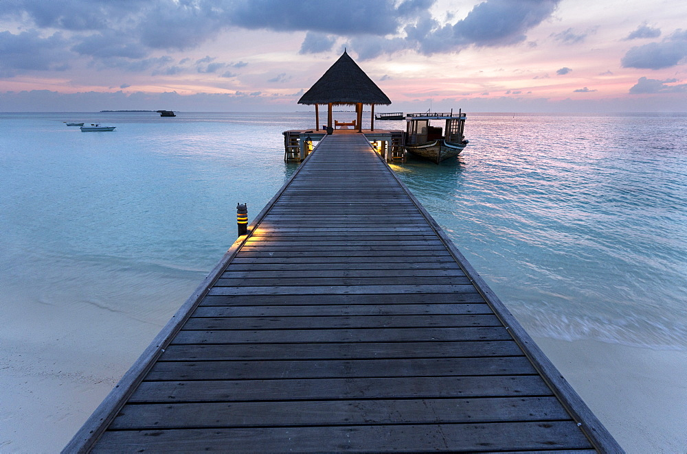 Wooden jetty and boat at sunset, Coco Palm Resort, Dhuni Kolhu, Baa Atoll, Republic of Maldives, Indian Ocean, Asia