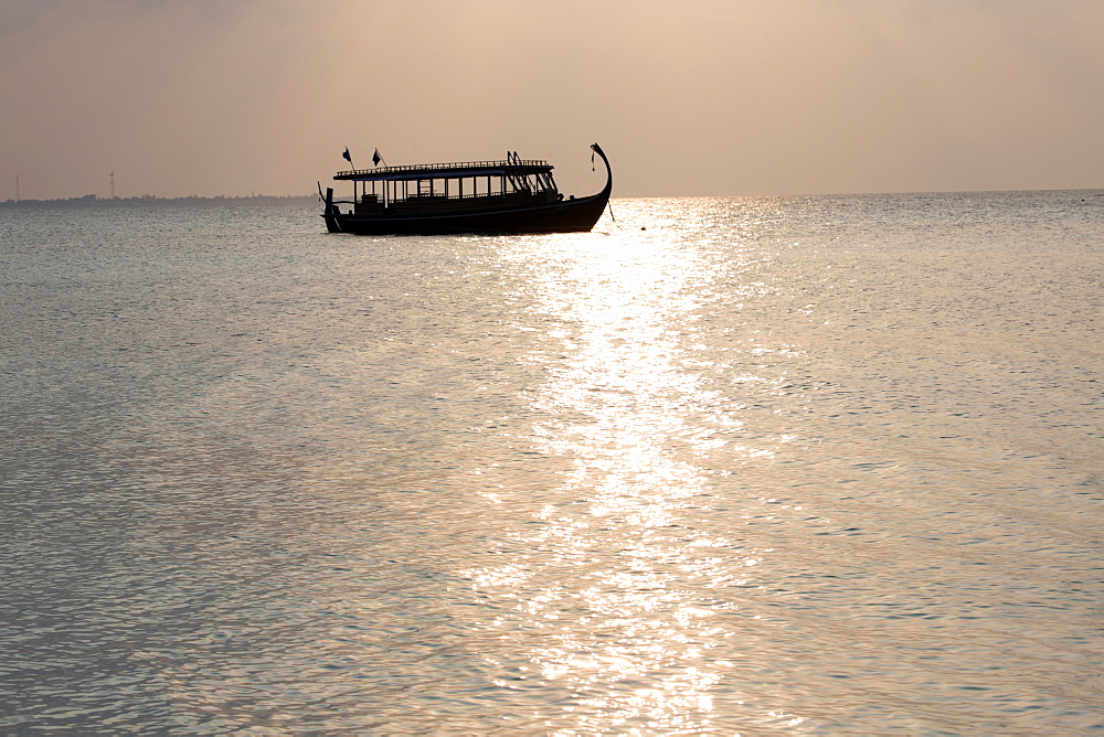 Wooden boat in silhouette at sunset, off Dhuni Kolhu, Baa Atoll, Republic of Maldives, Indian Ocean, Asia