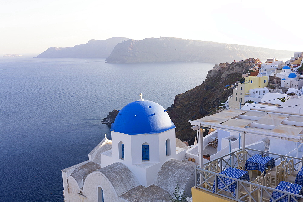 Evening view over the Caldera from Oia with blue domed church and distant volcanic cliffs, Santorini, Greek Islands, Greece, Europe