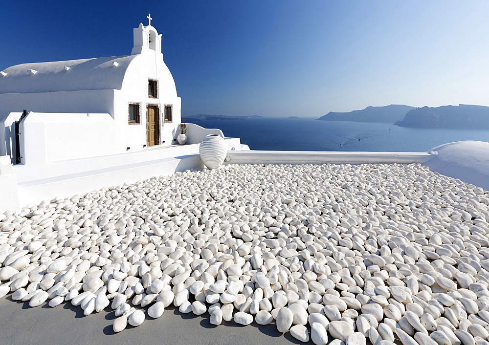 Small whitewashed church against blue sea and sky, Finikia, near Oia, Santorini, Cyclades, Greek Islands, Greece, Europe