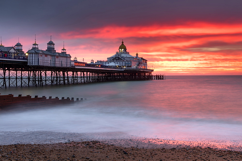 Eastbourne Pier against fiery red sky at sunrise, Eastbourne, East Sussex, England