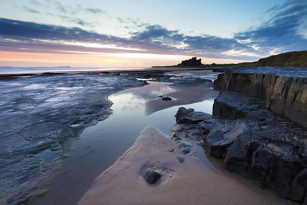 View towards Bamburgh Castle at sunrise from Bamburgh Beach, Bamburgh, Northumberland, England, United Kingdom, Europe
