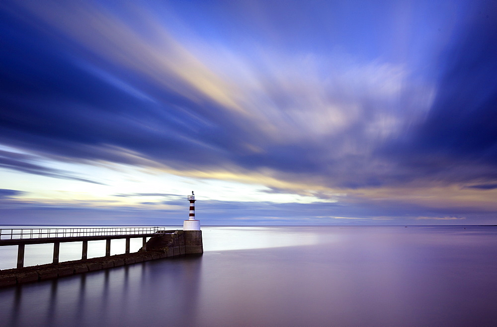 Long exposure image of Amble Lighthouse with streaky clouds and smooth sea, Amble, Northumberland, England