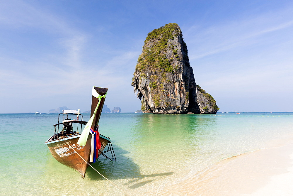 Traditional Longtail boat moored by Phra Nanag Beach with limestone islands in the background, Krabi, Thailand