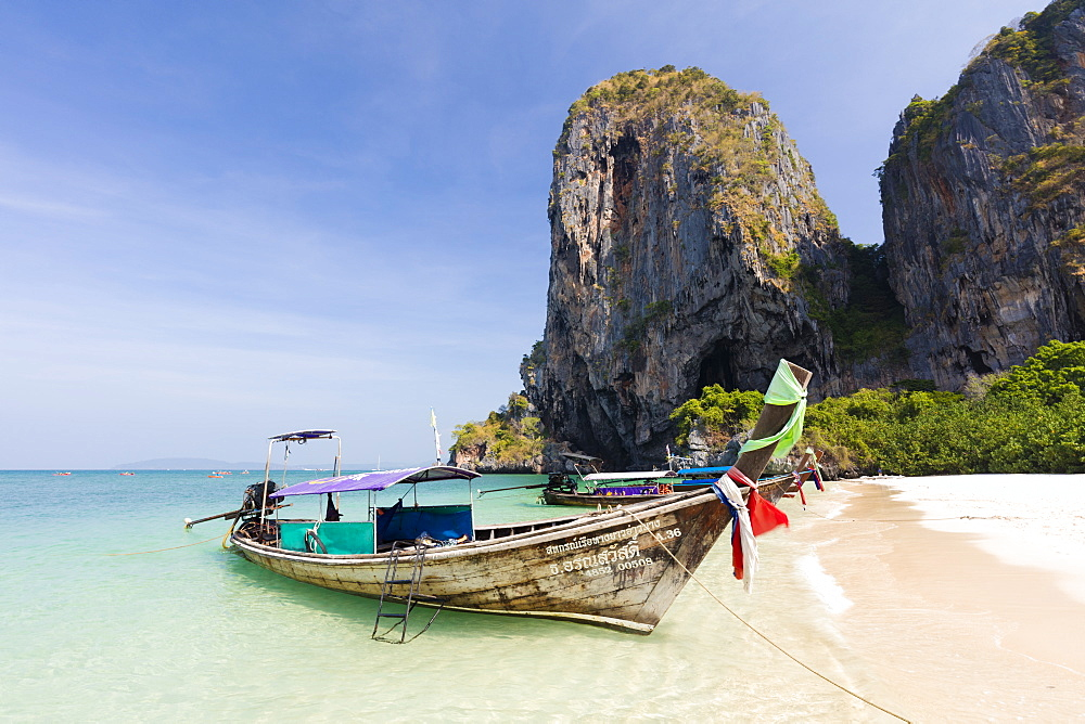 Traditional Longtail boats moored by Phra Nanag Beach with limestone cliffs in the background, Krabi, Thailand